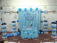 Little Man Stage Setup includes Blue Pompoms, Blue White & Silver metallic balloon pillars, Streamers and a Happy Birthday Bunting for the backdrop, Blue Tutu table cover, Hats and Center pieces