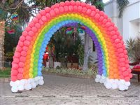 Rainbow balloon arch entrance to a theme birthday party made of 7 separate arches
