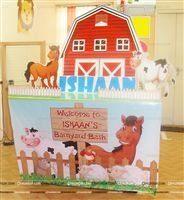 Cake table setup for small house parties with a 3 feet red barn cutout along with relatively sized cutouts of a horse and cow. The table is fenced with wood pegs to represent the farm.