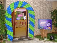Krishna theme birthday Entrance decor with balloon arch made of green and blue balloons and a welcome poster personalised with the baby name