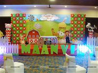 Birthday stage setup with a Barnyard banner, Shaped foil balloons of a Cow and Pig on pillars and a picket fence on the stage front along with the baby name in large alphabet cutouts.