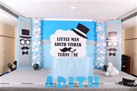 Stage setup includes a main backdrop, two side wings on either side, a tutu cover cake table with a center piece and the baby name alphabets cutouts.