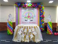 Pastel shades of fabric and balloons around a Unicorn banner. Table cover for the Cake table with personalized buntings and two cutouts of Unicorns on either side.