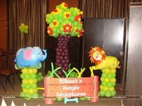 Jungle photo booth completely made with balloons that includes a fruiting tree, a Lion & Elephant foil balloon on a green balloon pillar along with a cutout that contains the little ones name.